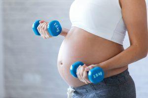 Mujer embarazada haciendo pesas